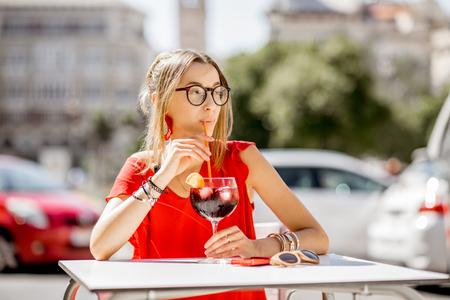 Jonge dame in rode jurk drinken sangria, traditionele Spaanse alcohol drinken gemaakt van wijn, buiten zitten in het restaurant