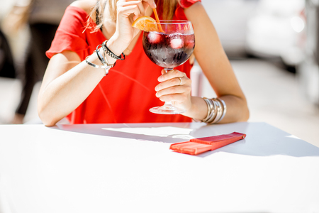 Woman holding a glass with Sangria, traditional spanish alcohol beverage made of wine, sitting outdoors at the restaurant. Image with no face focused on the glass