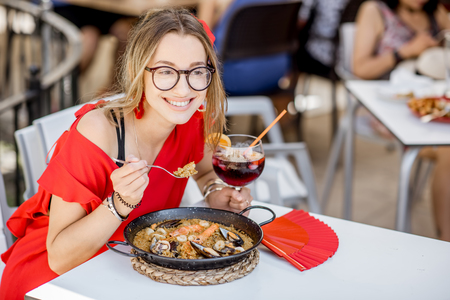 Young woman in red dress eating sea Paella, traditional Valencian rice dish, sitting outdoors at the restaurant in Valencia, Spain