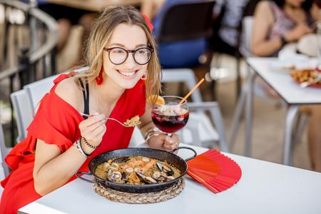 Junge Frau im roten Kleid, das Meer Paella, traditioneller Valencian-Reisteller, draußen sitzend im Restaurant in Valencia, Spanien isst Standard-Bild