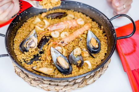 海のパエリア、バレンシアの米料理、屋外の白いテーブルの上のパンします。 写真素材 - 88321656