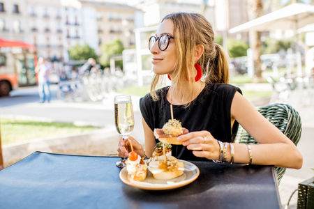 Young woman enjoying tasty appetizer with pinchos, traditional spanish snack, with glass of wine sitting outdoors at the bar in Valencia city Stock fotó
