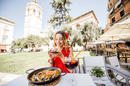 Young woman in red dress photographing sea Paella, traditional Valencian rice dish, sitting outdoors at the restaurant in Valencia