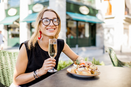 Young woman enjoying tasty appetizer with pinchos, traditional spanish snack, and glass of wine sitting outdoors at the bar in Valencia city Stock fotó