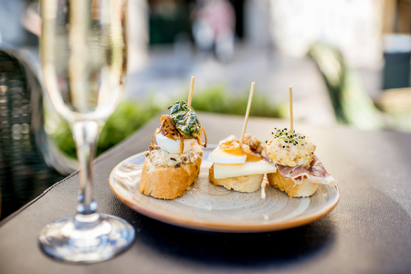 Young woman enjoying tasty appetizer with pinchos, traditional spanish snack, and glass of wine sitting outdoors at the bar in Valencia city 写真素材