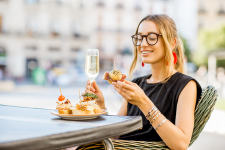 Young woman enjoying tasty appetizer with pinchos, traditional spanish snack, with glass of wine sitting outdoors at the bar in Valencia city 스톡 콘텐츠