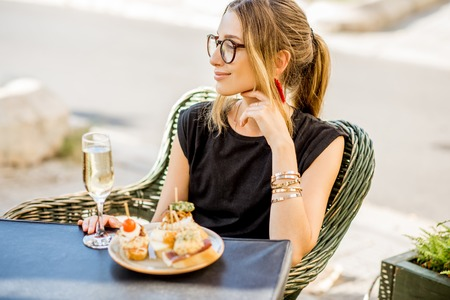 Young woman enjoying tasty appetizer with pinchos, traditional spanish snack, with glass of wine sitting outdoors at the bar in Valencia city Stock Photo