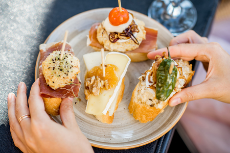 Beautiful and colorful set of pinchos, traditional spanish snack related to tapas, outdoors on the table 스톡 콘텐츠