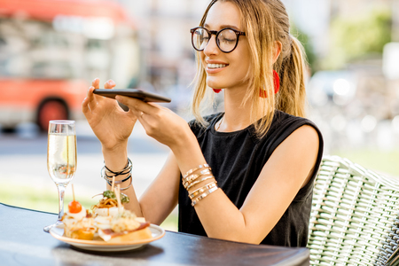 Young woman photographing with phone pinchos, traditional spanish snack, with glass of wine sitting outdoors at the bar in Valencia city