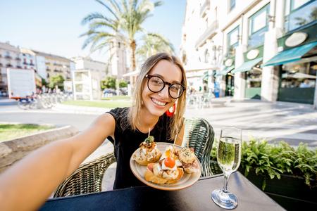 pinchos, 전통적인 스페인 스낵, 그리고 발렌시아 도시에서 술집에서 야외에 앉아 와인 잔의 셀프 사진 만들기 젊은 여자