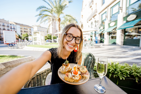 Young woman making selfie photo with pinchos, traditional spanish snack, and glass of wine sitting outdoors at the bar in Valencia city Фото со стока