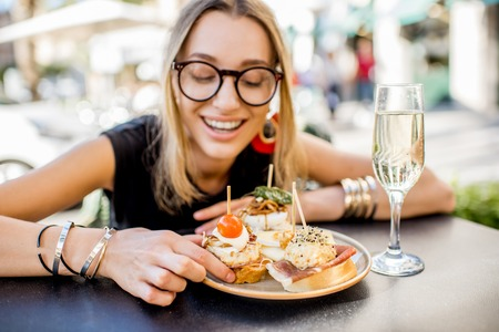 Young woman enjoying tasty appetizer with pinchos, traditional spanish snack, and glass of wine sitting outdoors at the bar in Valencia city 스톡 콘텐츠