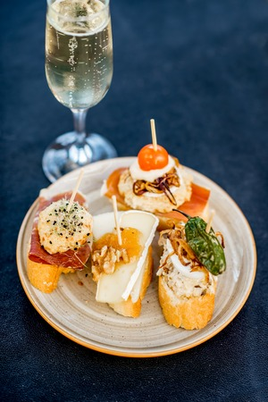 Beautiful and colorful set of pinchos, traditional spanish snack related to tapas, with glass of wine outdoors on the table