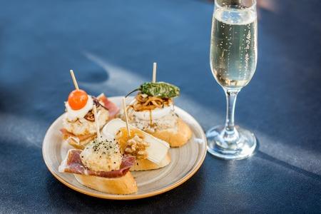 Mooie en kleurrijke reeks pinchos, traditionele Spaanse snack met betrekking tot tapas, met glas wijn in openlucht op de lijst