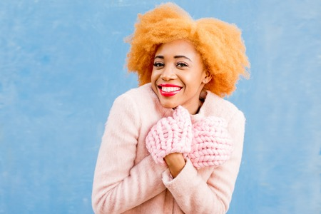 Portrait of a cute african woman in the pink coat and knitted gloves on the blue wall background. Winter season concept Stock Photo