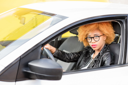 Portrait of a beautiful african woman in leather jacket sitting in the car on the yellow background