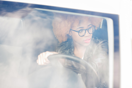 View through the car windscreen on a beautiful african woman driving a car Stock Photo