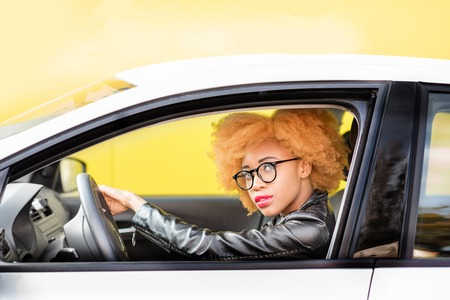 Portrait of a beautiful african woman in leather jacket driving a car on the yellow background