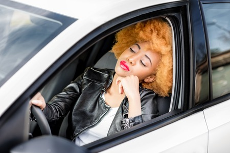 Young african woman in leather jacket feeling sleepy while driving the car