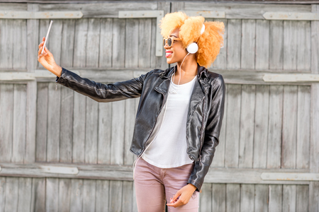 Lifestyle portrait of an african woman in leather jacket making selfie photo with phone standing on the wooden wall background