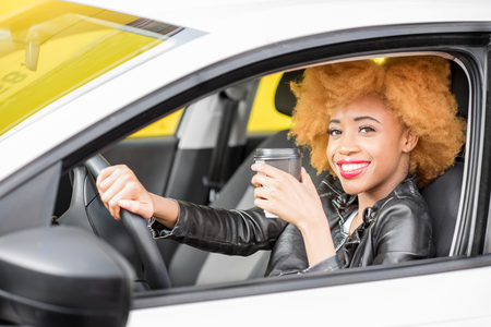 Portrait of a beautiful african woman in leather jacket with coffee cup sitting in the car on the yellow background Stock Photo