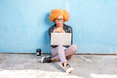 African woman with curly hair working with laptop sitting on the blue wall background