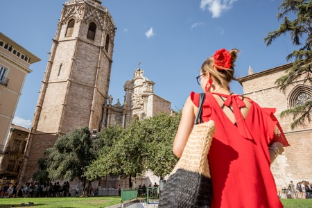 Young woman tourist in red dress walking on the central square near the main cathedral in Valencia city, Spain