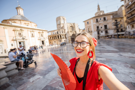 Selfie portrait of a young woman tourist in red dress with hand fan on the central square of the old town in Valencia city, Spain