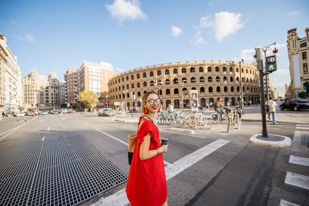Junge Frau im roten Kleid gehend die Straße nahe dem Stierkampfarena-Amphitheater in Valencia-Stadt, Spanien Standard-Bild - 89744869