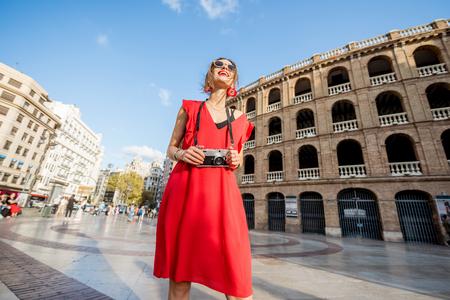 Porträt des Touristen der jungen Frau im roten Kleid, das mit Fotokamera vor dem Stierkampfarenaamphitheater in Valencia-Stadt, Spanien steht Standard-Bild - 89744871