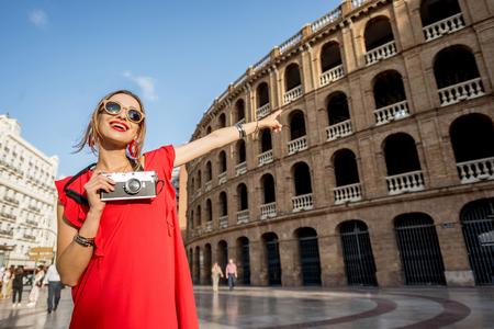 Porträt des Touristen der jungen Frau im roten Kleid, das mit Fotokamera vor dem Stierkampfarenaamphitheater in Valencia-Stadt, Spanien steht Standard-Bild - 89744885
