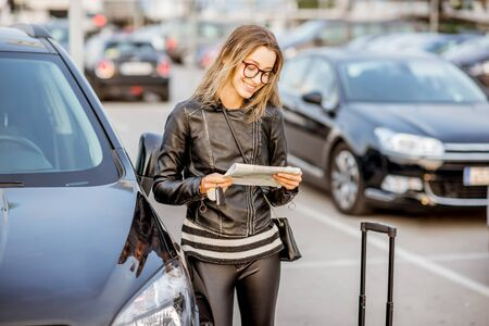 Young woman looking on the rental contract standing outdoors on the airport car parking Stock Photo