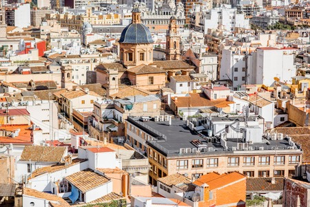 Top cityscape view on the old residential buildings with church in Valencia city during the sunny day in Spain