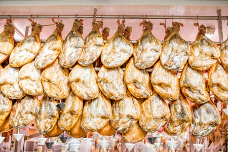 Jamon, pernas de porco espanhol tradicional, pendurado na loja de mercado em Valência, Espanha Foto de archivo - 88758145