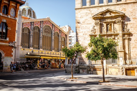 Street view with saint Joan church and famous food market Central in Valencia city, Spain