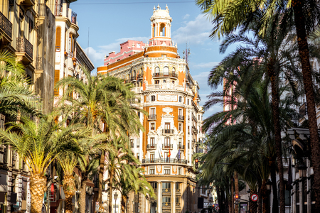 Street view with beautiful luxurious building and palm trees in Valencia city during the sunny day in Spain