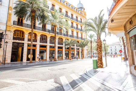 Street view with beautiful buildings and palm trees in Valencia city in Spain