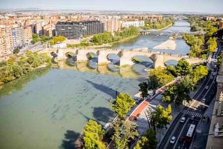Aerial cityscape view on Elbe river with stone bridge in Zaragoza city in Spain Foto de archivo