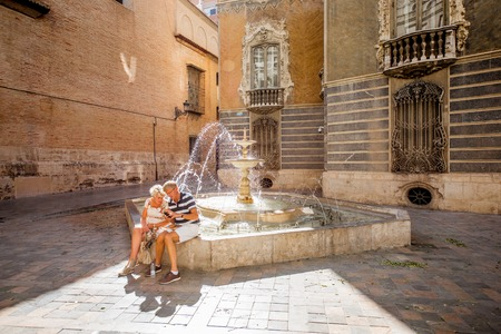 VALENCIA, SPAIN - August 18, 2017: View on the national museum of ceramics and decorative arts with elder couple sitting on the fountain in Valencia city, Spain 新聞圖片