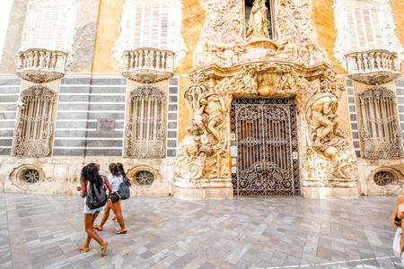 VALENCIA, SPAIN - August 18, 2017: View on the national museum of ceramics and decorative arts with african ethnicity girls walking in Valencia city, Spain