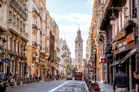 VALENCIA, SPAIN - August 18, 2017: View on the central street with Catalina tower crowded with people and transport in Valencia old town during the sunny weather