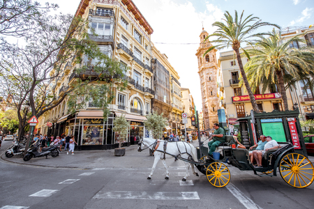 VALENCIA, SPAIN - August 18, 2017: Street view with old buildings and Catalina tower crowded with people and carriage in Valencia city, Spain