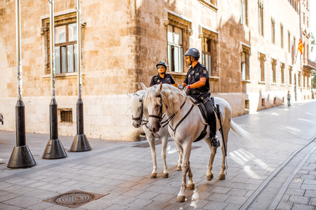 VALENCIA, SPAIN - August 19, 2017: Police patrol riding horseback on the central street of the old town of Valencia city in Spain