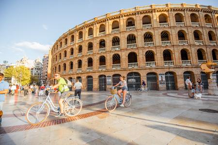VALENCIA, SPANIEN - 18. August 2017: Straßenansicht mit dem Stierkampfarengebäude und den Leuten, die Fahrrad auf das Toros-Quadrat in Valencia City in Spanien fahren Standard-Bild - 88661557