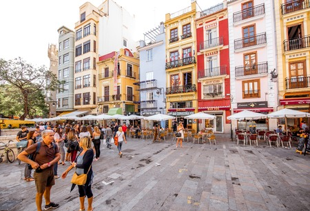 VALENCIA, SPAIN - August 19, 2017: Colorful buildings with cafes and restaurants crowded with tourists near the food market in Valencia city, Spain 新聞圖片
