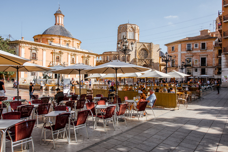 VALENCIA, SPAIN - August 18, 2017: View on the Virgen square with cafe terrace and cathedral on the background in Valencia city, Spain Редакционное