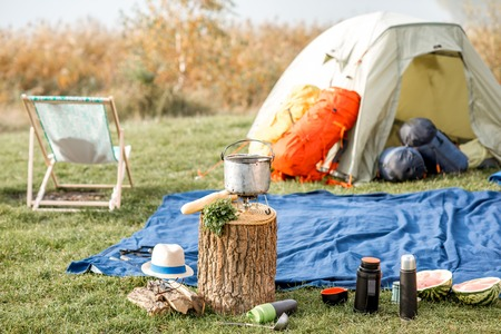 Camping place with tent, backpacks, chair and hiking equipmment outdoors on the green lawn