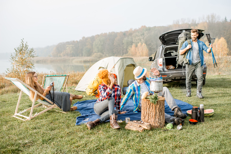 Multi ethnic group of friends dressed casually having a picnic during the outdoor recreation with tent, car and hiking equipment near the lake