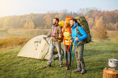 緑の芝生でキャンプの近くに立って、バックパックとハイキングにカラフルなジャケットに多民族の友人