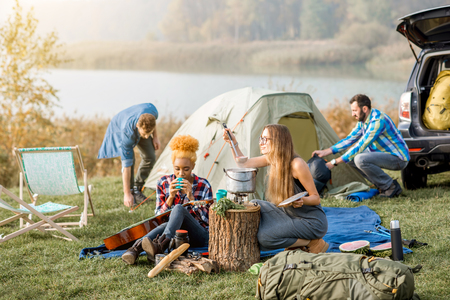 Multi ethnic group of friends dressed casually having a picnic, cooking soup with cauldron during the outdoor recreation near the lake Stock Photo
